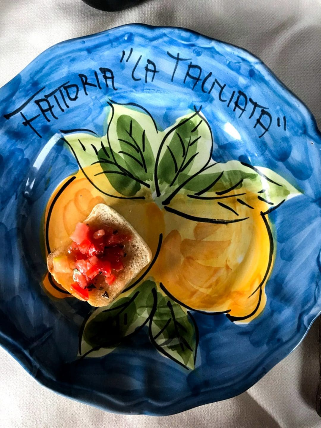 A painted plate sohowcasing lemons.
