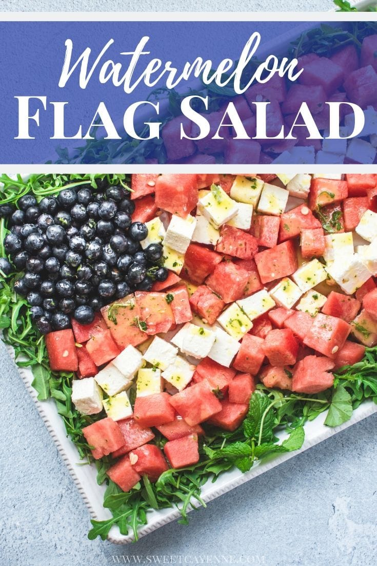A white platter with a red, white, and blue watermelon flag salad on top on a blue stone background.