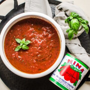An overhead shot of a white bowl with tomato pizza sauce and can of San Marzano tomatoes on the side.