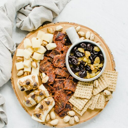 An overhead shot of a snacking board featuring beef jerky, crackers, dried fruit, cheese, and bananas topped with peanut butter and chocolate chips.