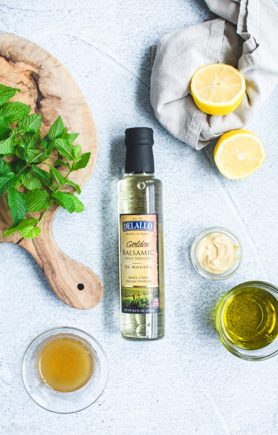 A bottle of Delallo white balsamic vinegar with ingredients for fresh mint vinaigrette on the side.