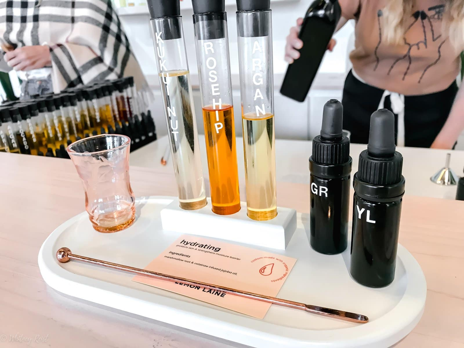 A tray with serums and ingredients and a mixer cup for making a custom facial oil.