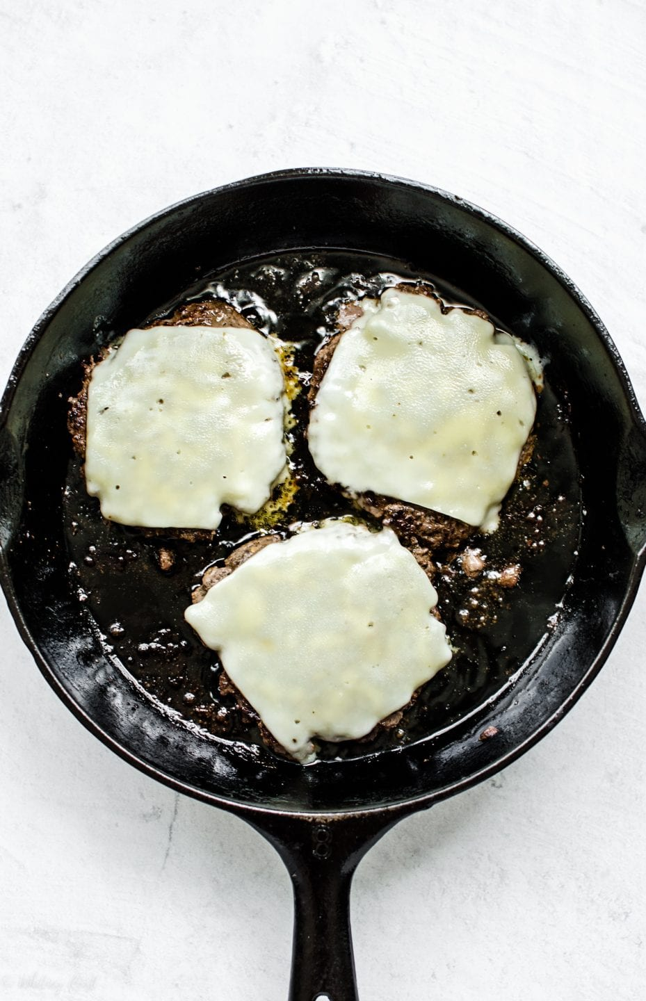Three mushroom smashburger patties in a cast iron skillet with melted Swiss cheese on top.