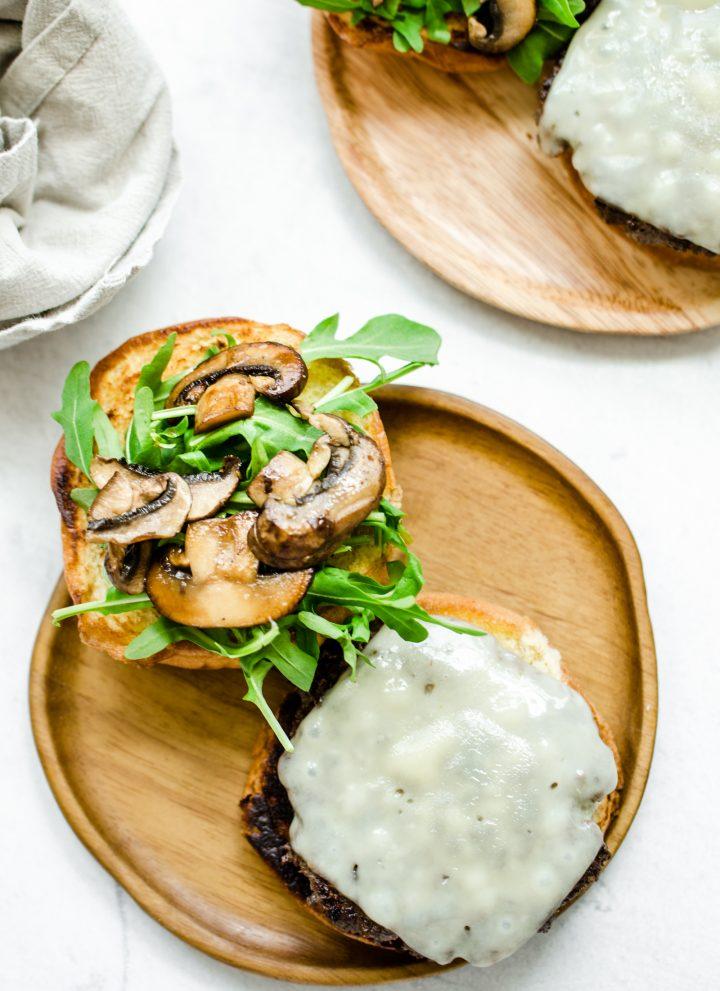An overhead shot of an open faced mushroom swiss smashburger on a wooden plate.