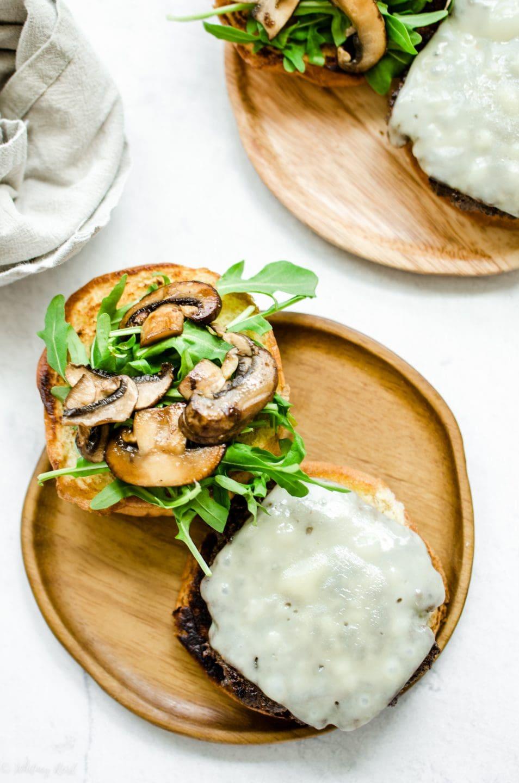 An open-faced mushroom swiss burger on a wooden plate.