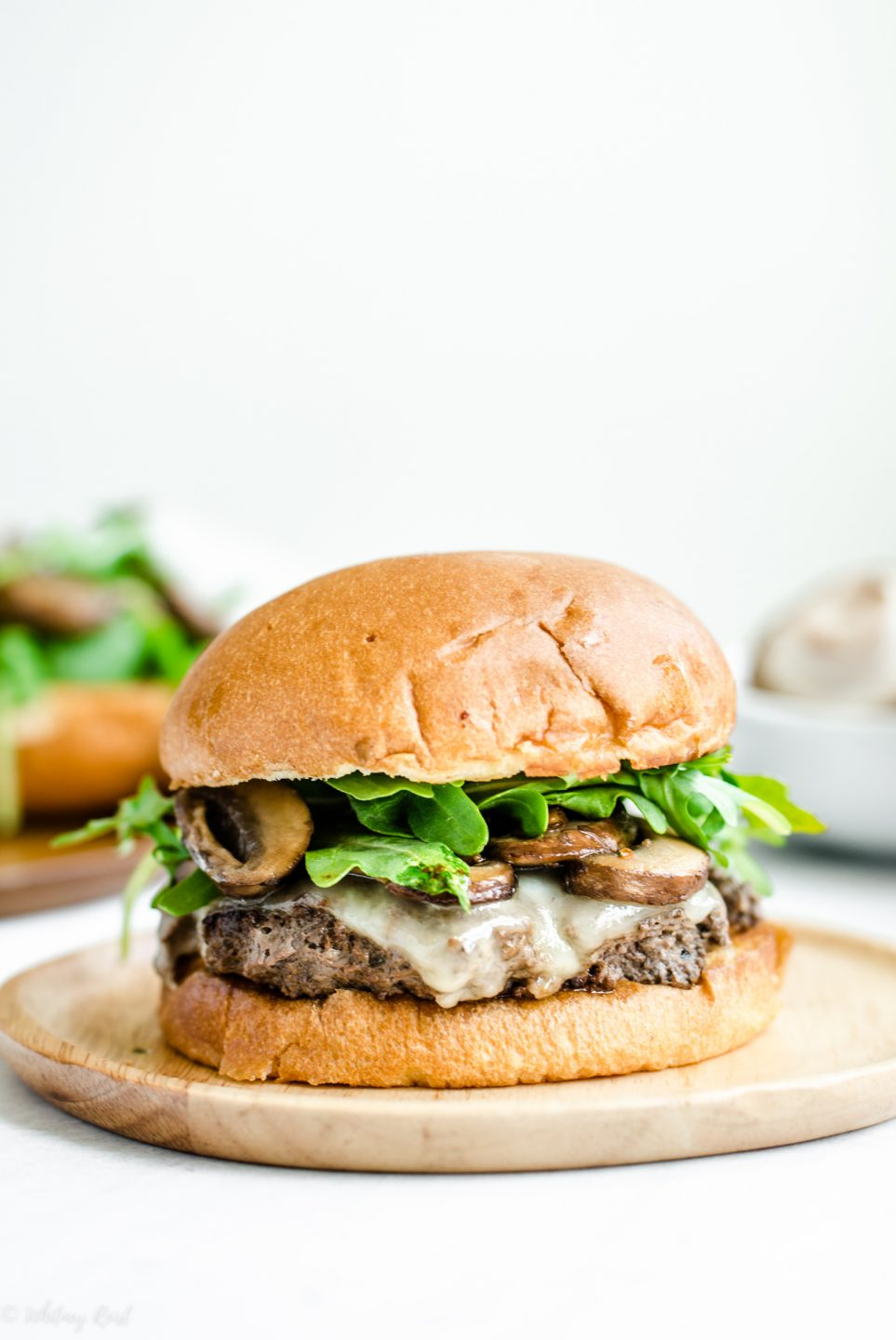 A mushroom swiss smashburger with arugula sitting on a wooden plate against a white backdrop.