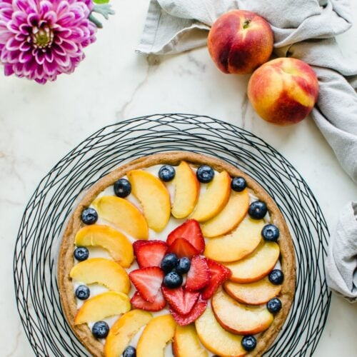 A peach fruit pizza on a wire charger with whole peaches and a vase of flowers on the side.