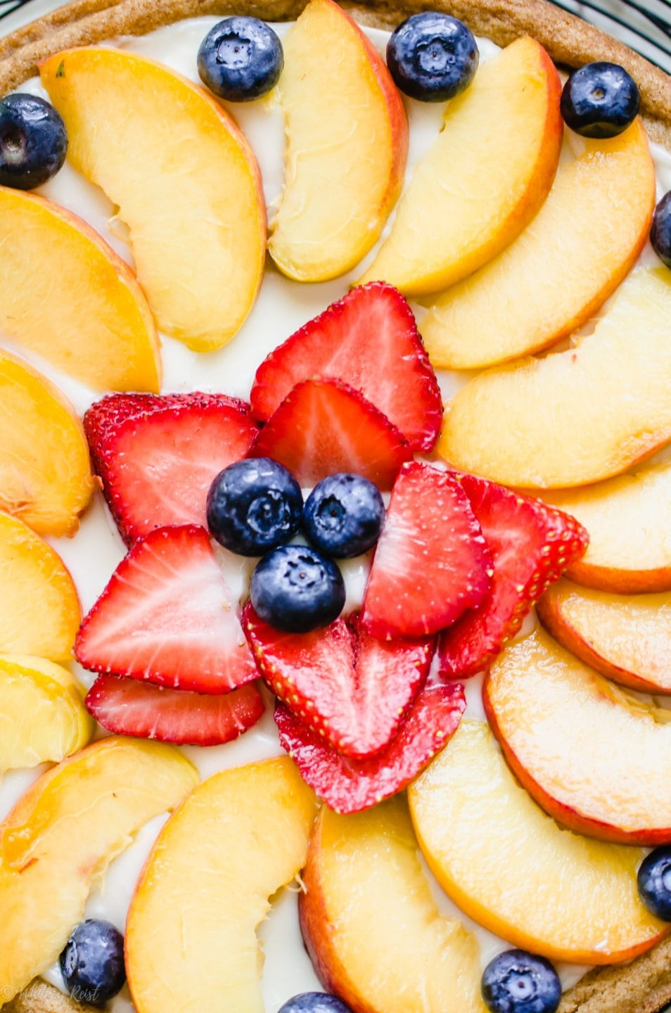 A close up shot of the middle of a decorated fruit pizza with peaches, strawberries, and blueberries.