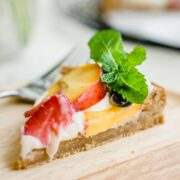A side angle shot of a slice of peach fruit pizza on a wooden plate garnished with a sprig of mint.