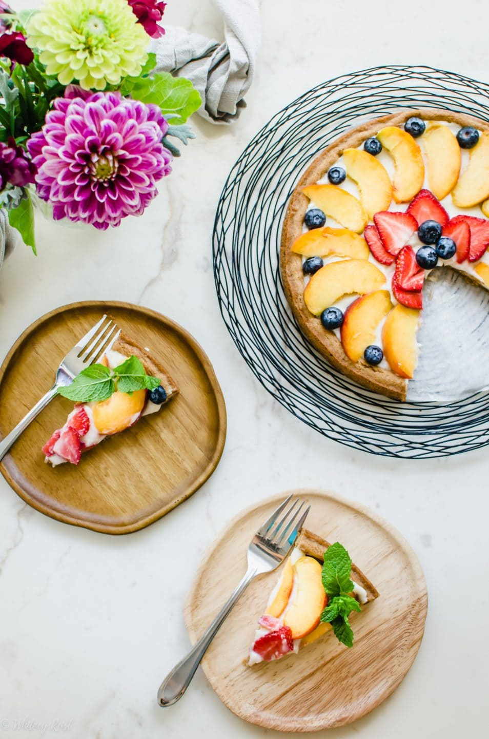 An overhead shot of two wooden plates of fruit pizza with forks and a vase of flowers.