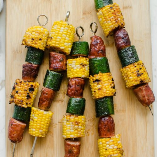 Grilled sausage, corn, and zucchini kabobs on a bamboo cutting board.