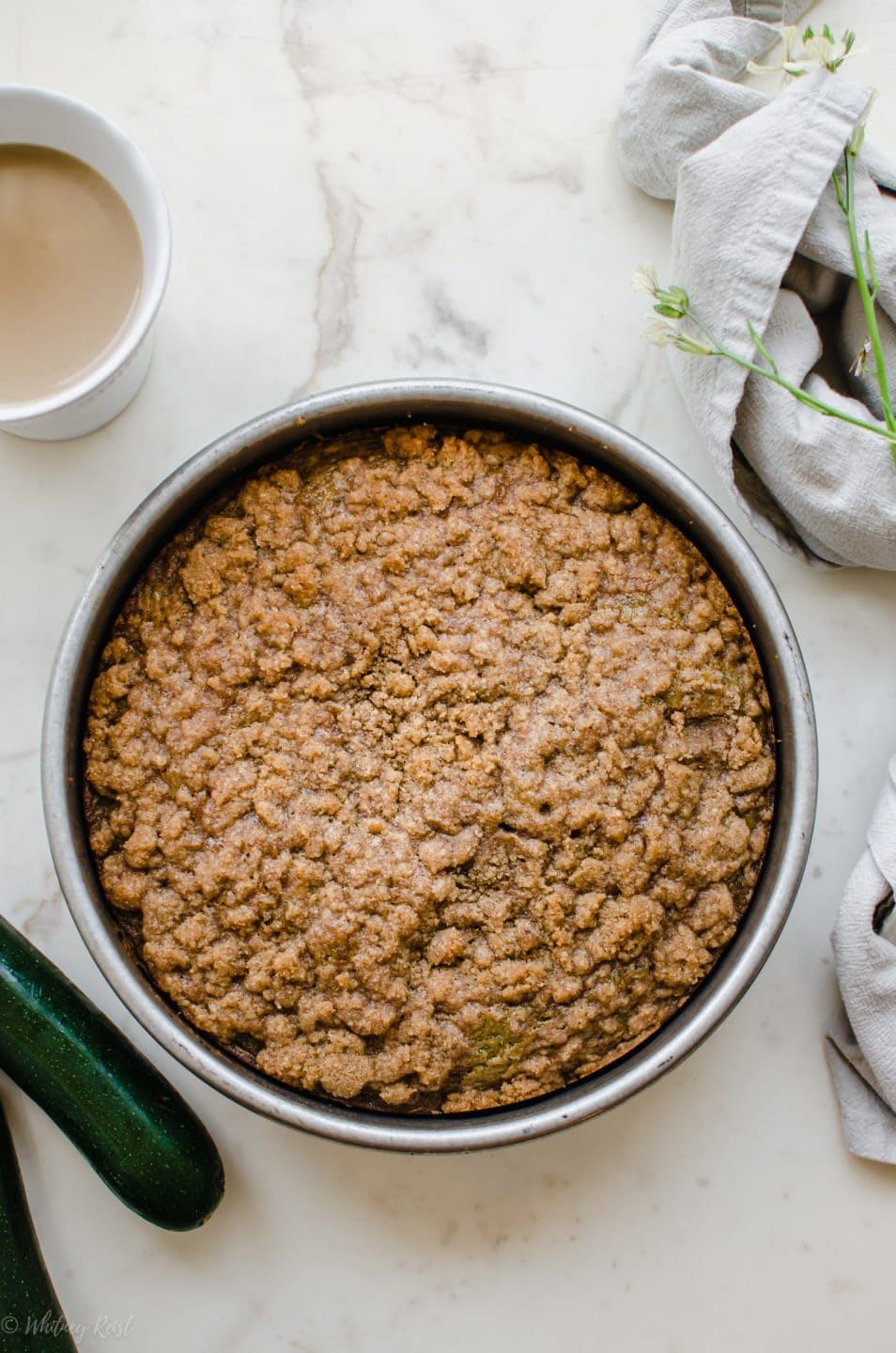 A zucchini coffee cake in a cake pan with a cup of coffee on the side.