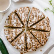 An overhead shot of a sliced zucchini coffee cake with a cup of coffee on the side.
