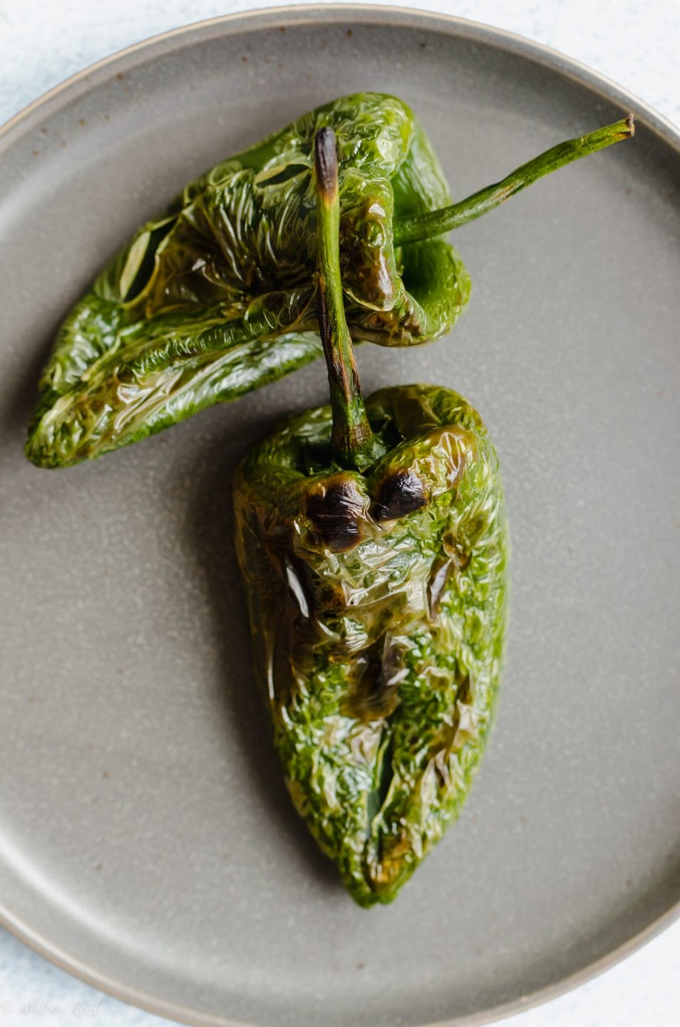 Two roasted poblano peppers on a grey slate plate.