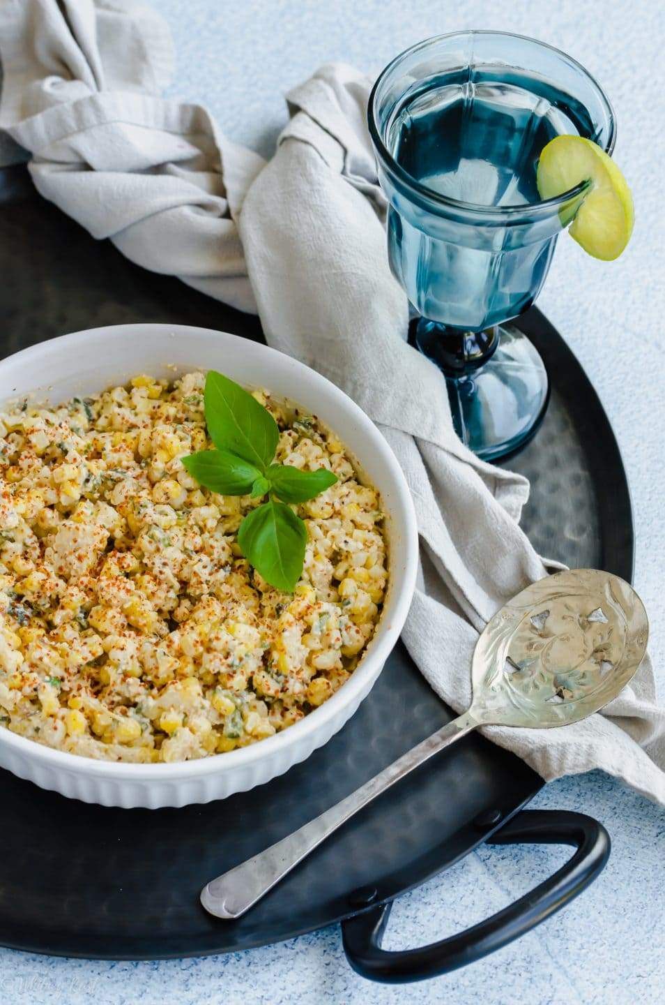 A bowl of elote-style corn on a black platter with a glass of blue water.