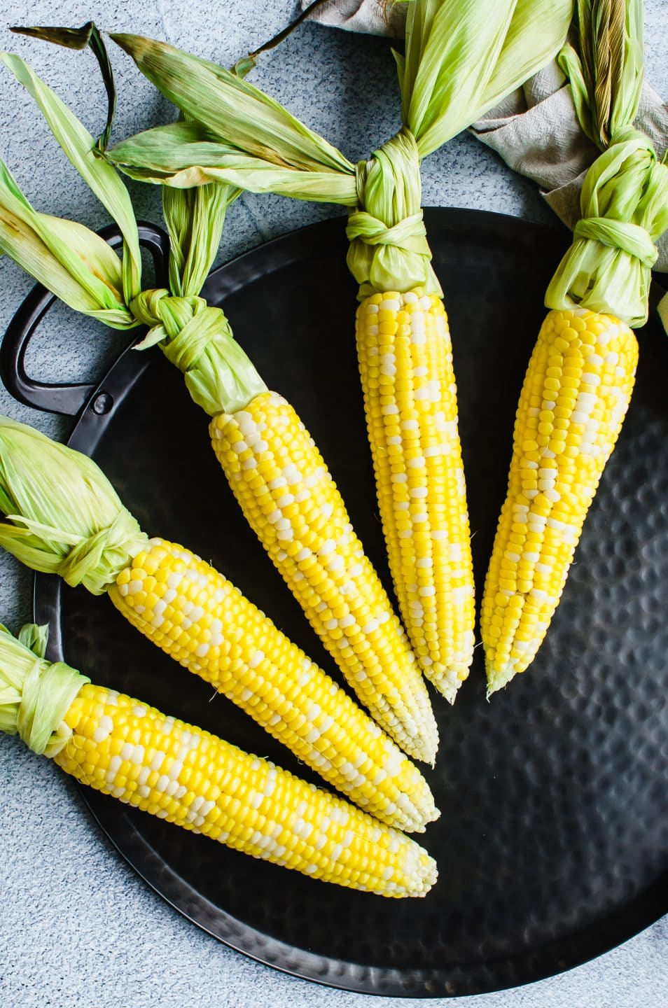 Raw corn on the cob on a black iron platter with the husks tied in knots.