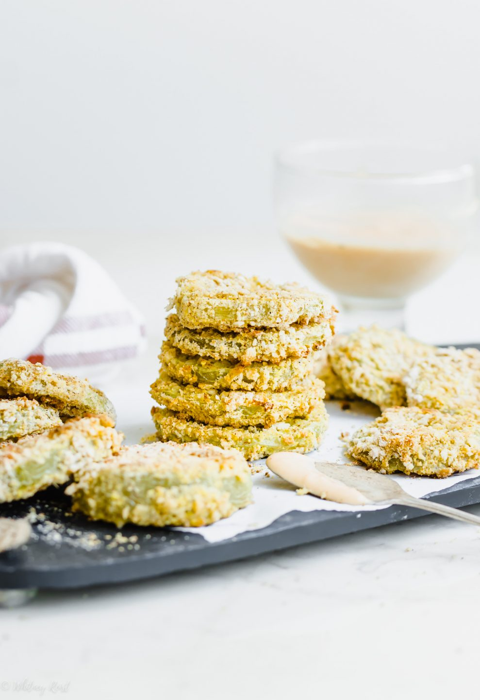 Oven-fried green tomatoes stacked on a slate platter with a bowl of hot sauce aioli on the side.