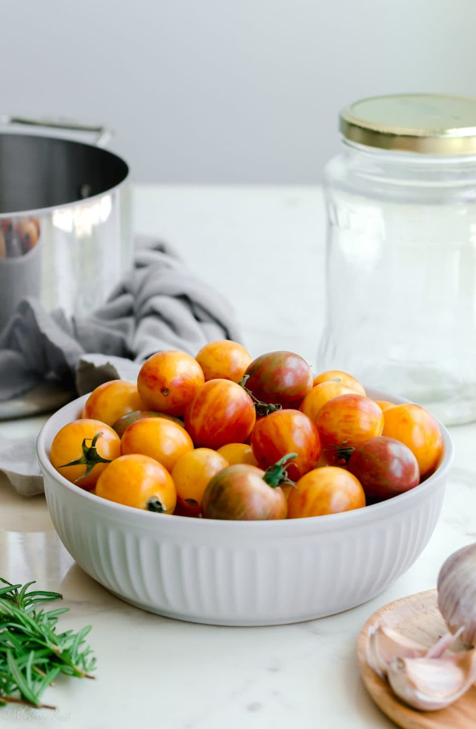 A straight-on shot of the jar, tomatoes, pot, rosemary, and garlic cloves needed for a pickled tomatoes recipe.