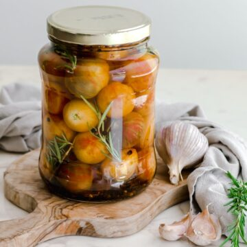 A large jar filled with pickled cherry tomatoes sitting on a cutting board.