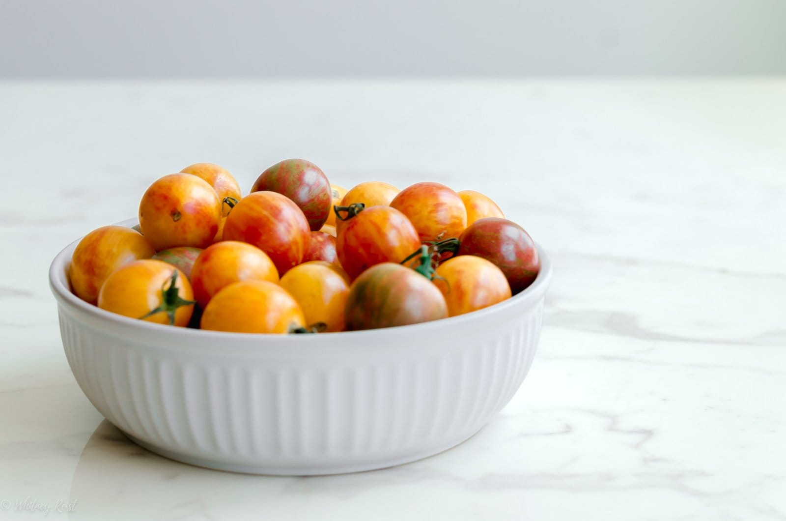 A side angle of tomatoes in a white bowl on a white marble countertop.