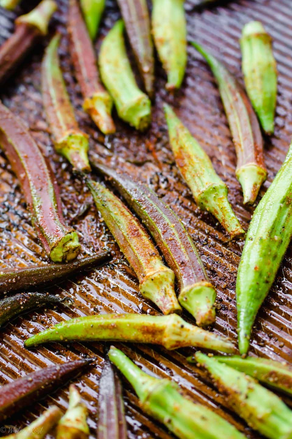 A baking sheet with raw okra pods and seasoning on top for roasting.