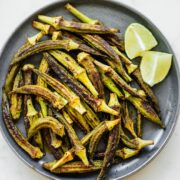 An overhead shot of a gray ceramic plate with roasted okra and lime wedges.