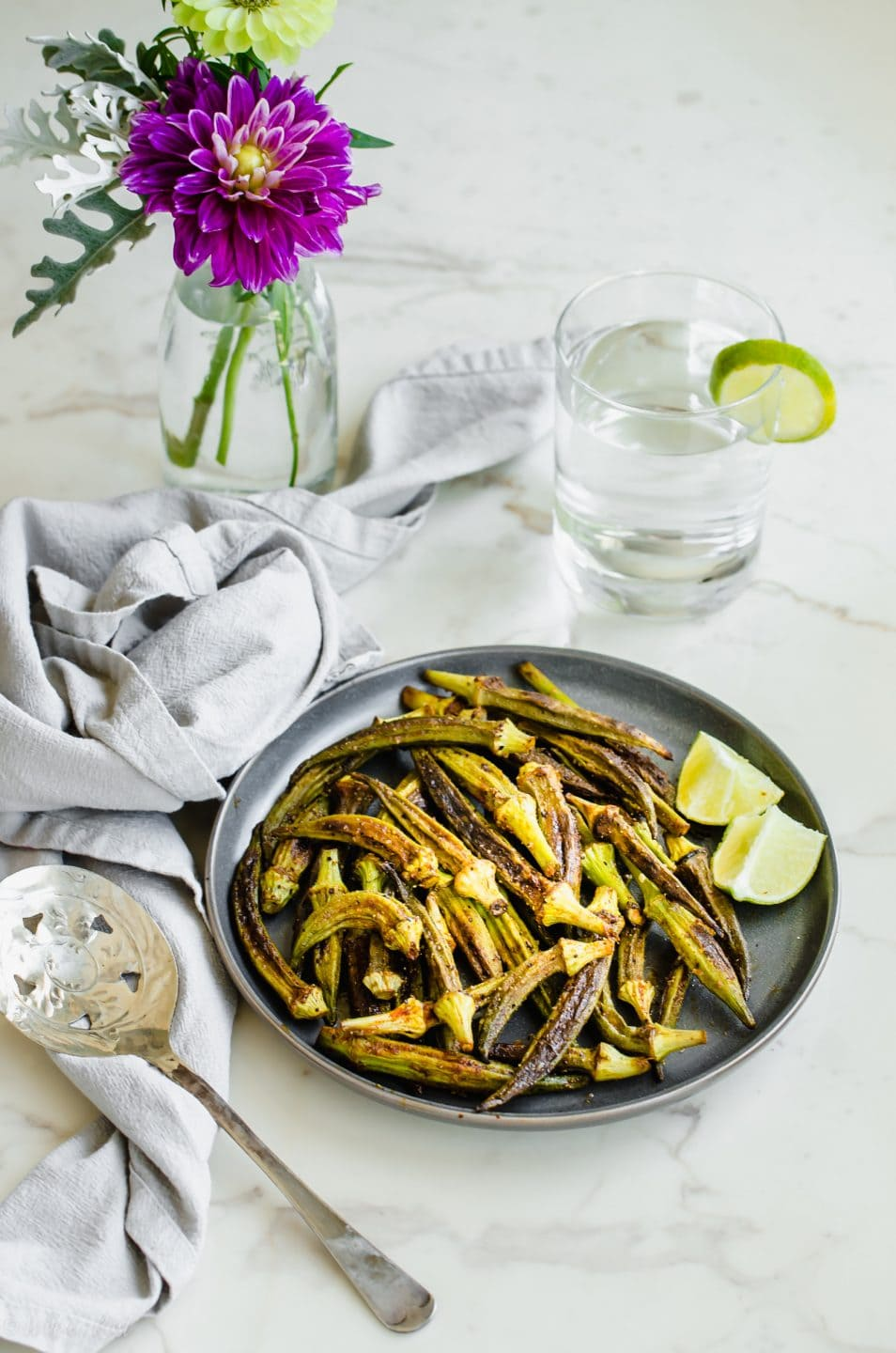 A gray plate with roasted okra and some fresh lime wedges on a white counter top.