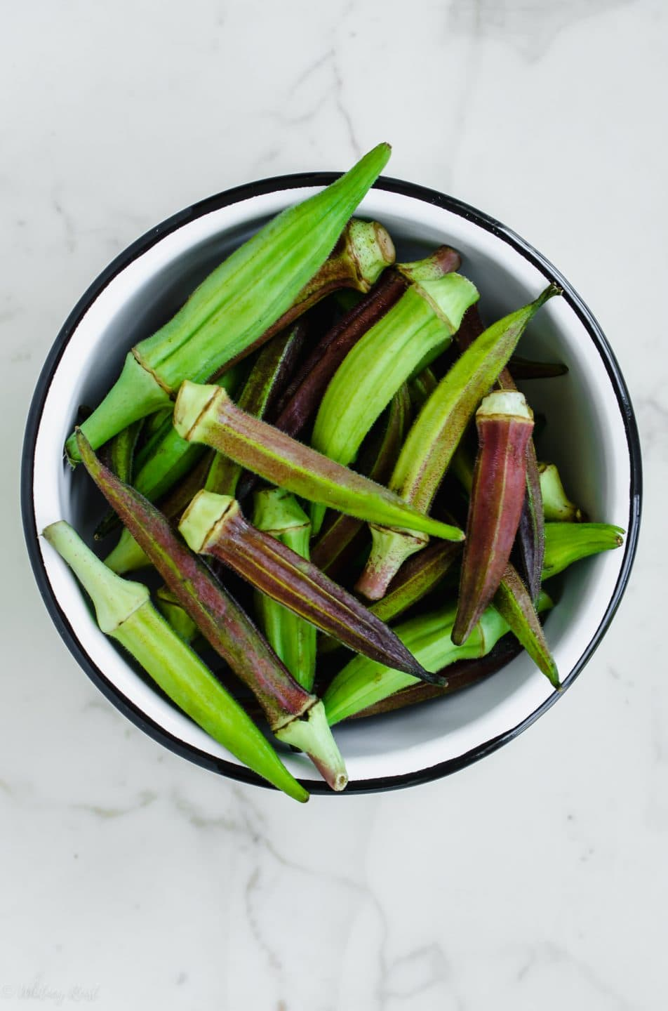 A white bowl filled with fresh okra pods on a white marble surface.