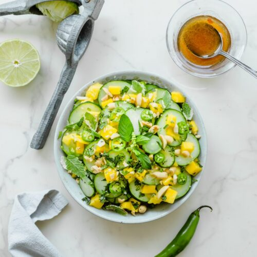 A grey bowl with Thai cucumber mango salad with a small dish of vinaigrette and fresh limes on the side.
