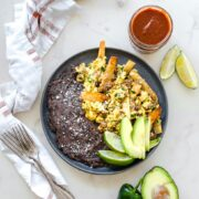 A grey plate with migas and refired black beans with a fork and jar of taco sauce on the side.