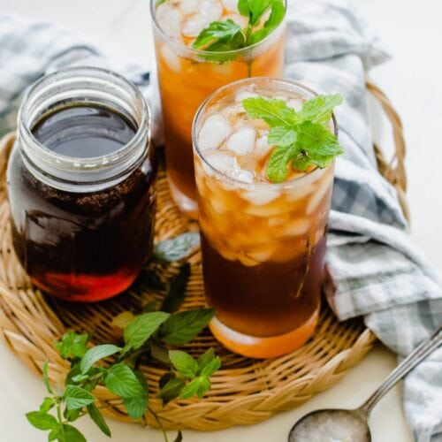 Two glasses of iced tea garnished with mint on a rattan wicker serving tray.