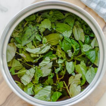 A bunch of fresh chopped mint in a saucepan filled with simple syrup.