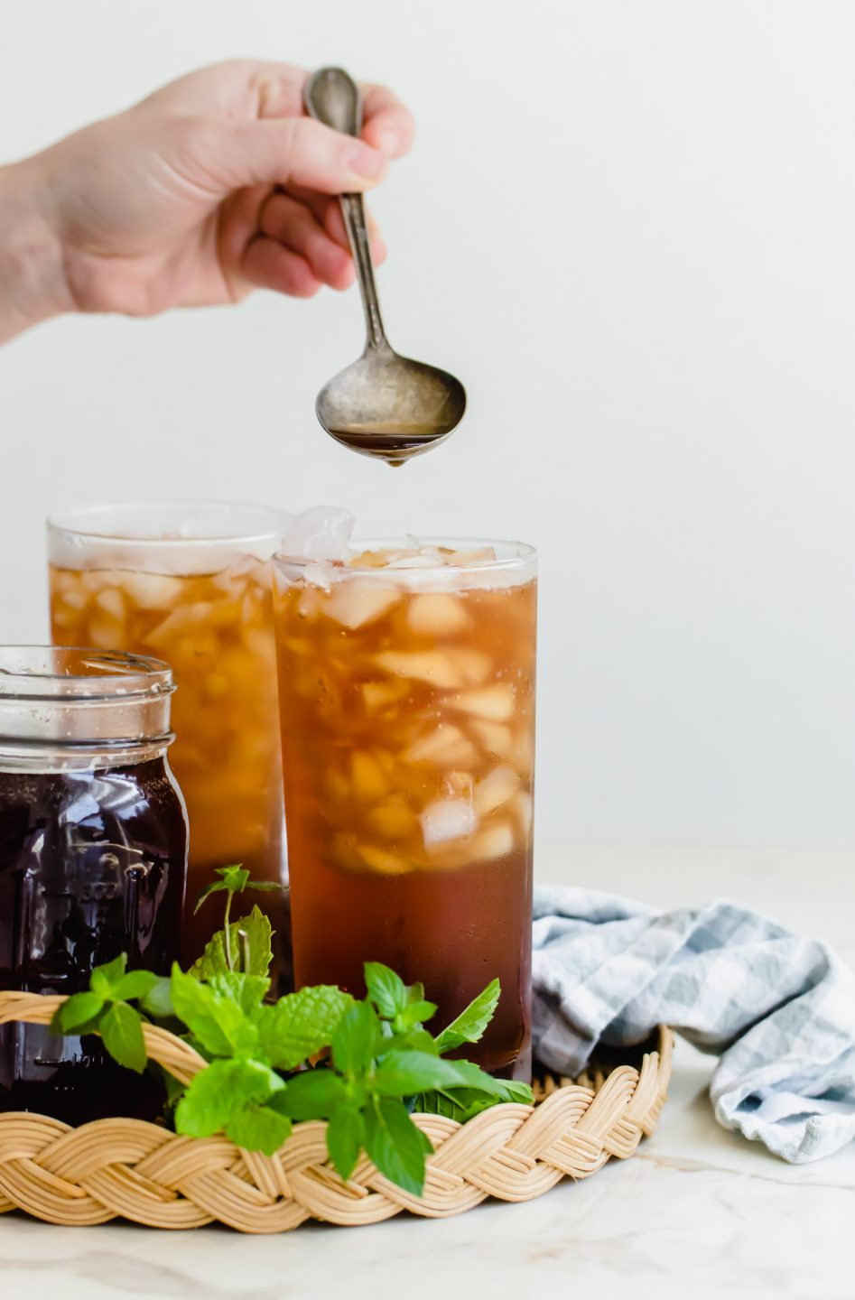 A hand spooning simple syrup into a full glass of iced tea.
