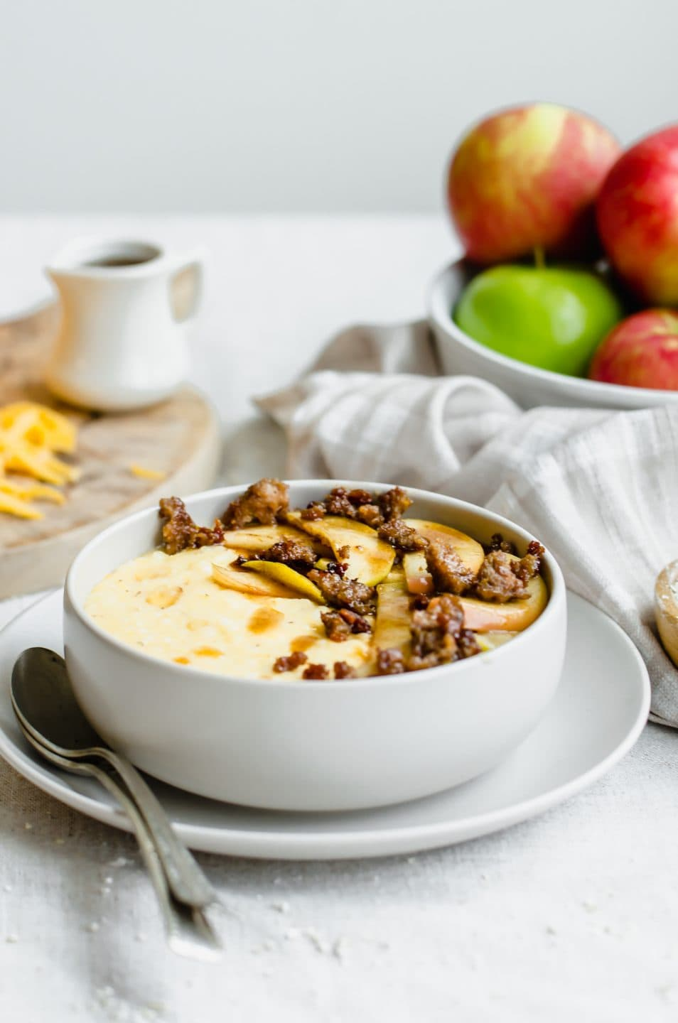 A grey bowl filled with cheddar grits, cinnamon apples, and sausage crumbles with a plate of apples in the back.