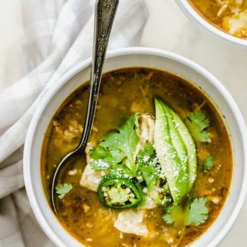 A white bowl of soup filled with posole verde and garnished with avocado and cilantro.