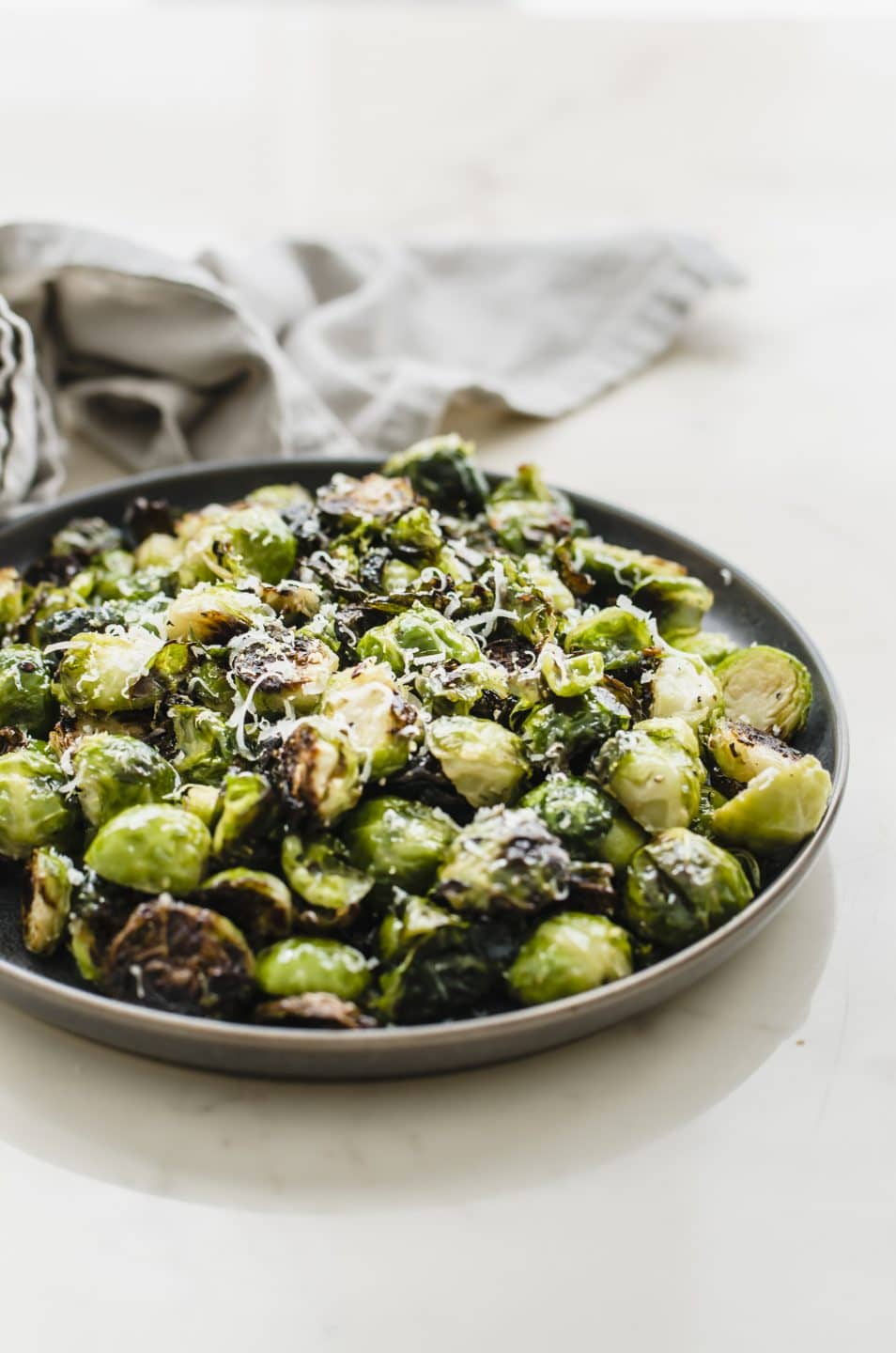 A grey plate filled with crispy roasted brussels sprouts on a marble countertop.