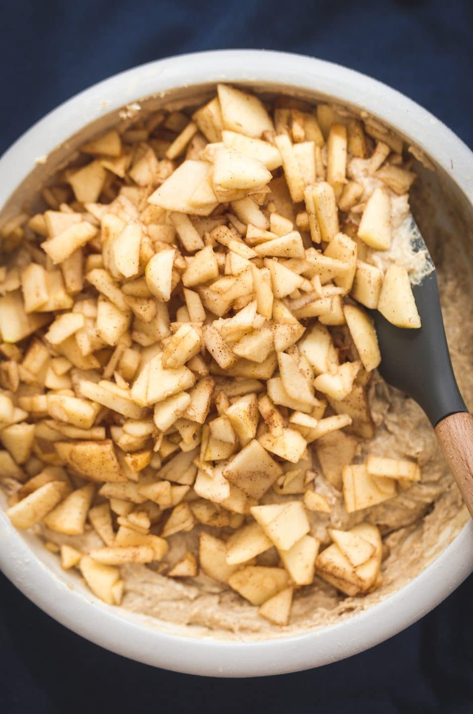 A white mixing bowl filled with cake batter and cinnamon apples being folded in.