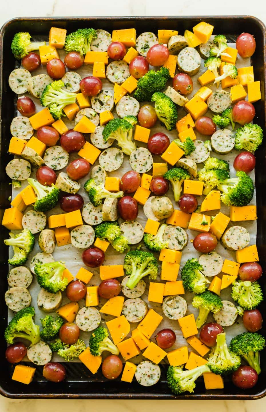 A sheet pan filled with cut veggies ready for roasting.