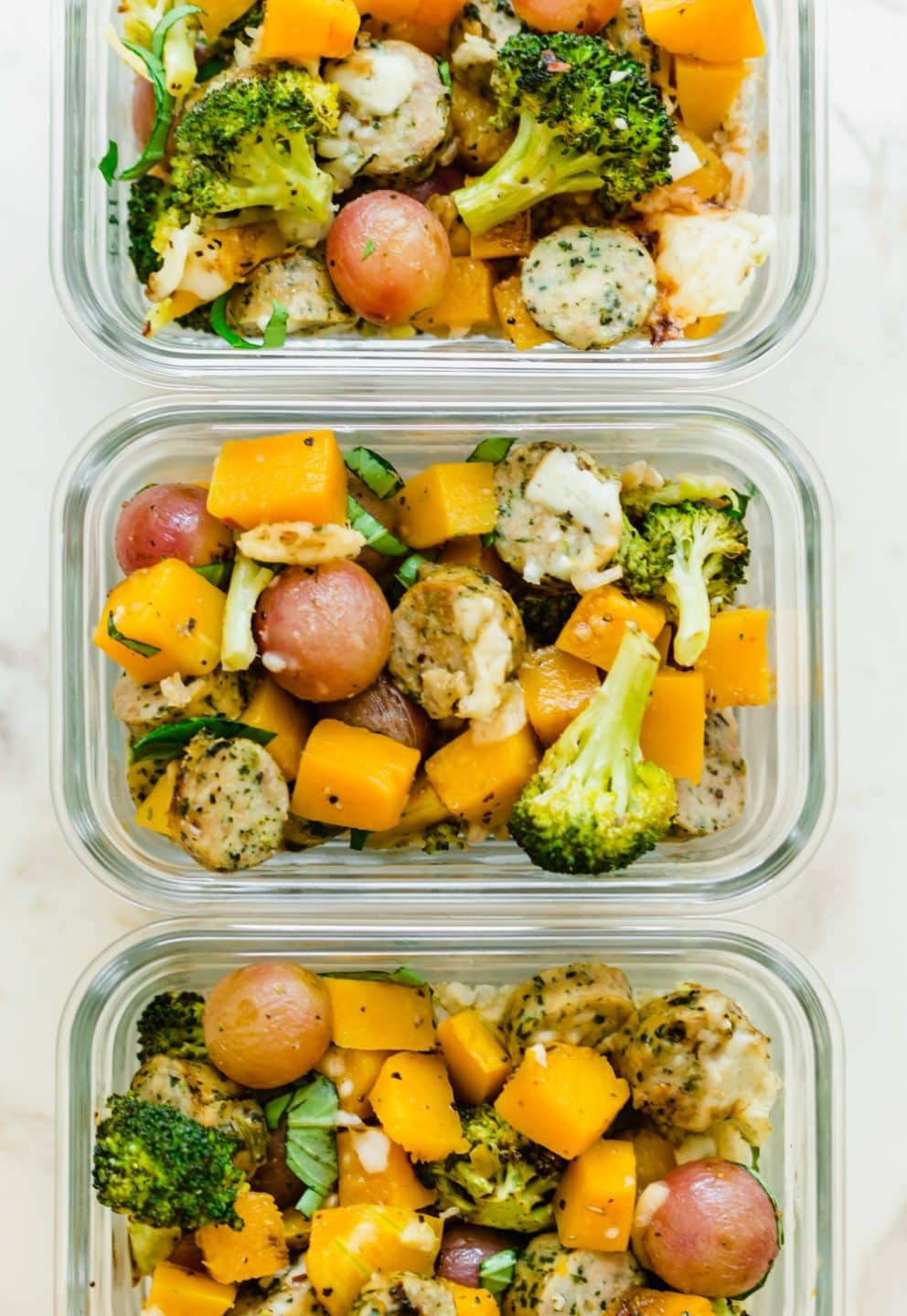 An overhead shot of glass meal prep containers filled with roasted veggies.