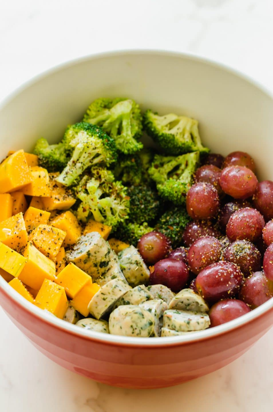 A large bowl filled with cut broccoli florets, cubed butternut squash, red grapes, and chicken sausage.