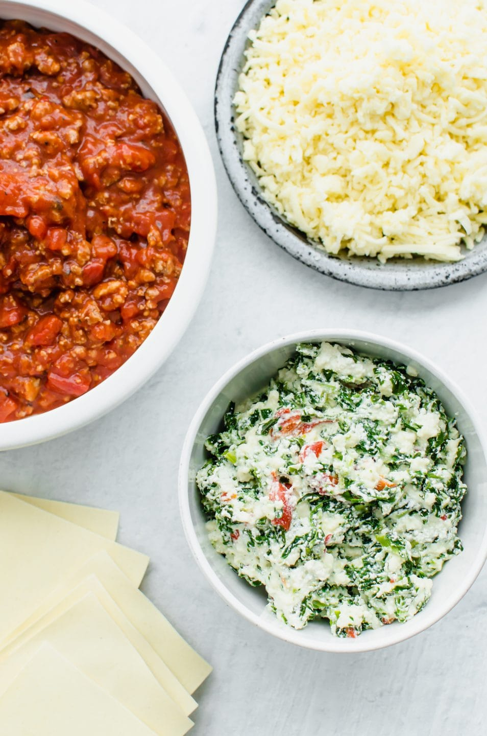 Prep bowls with ingredients for making Turkey Florentine Lasagna on a white stone background.