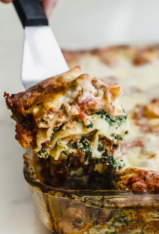 A spatula lifting a squash of lasagna out of a baking dish.