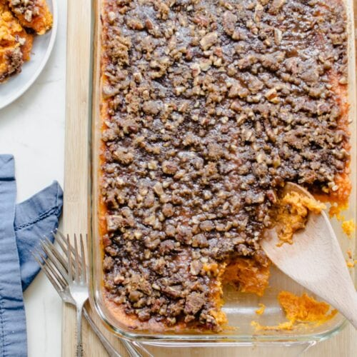 An overhead shot of a dish of Apple Cider Sweet Potato Casserole on a cutting board with a blue napkin on the side.