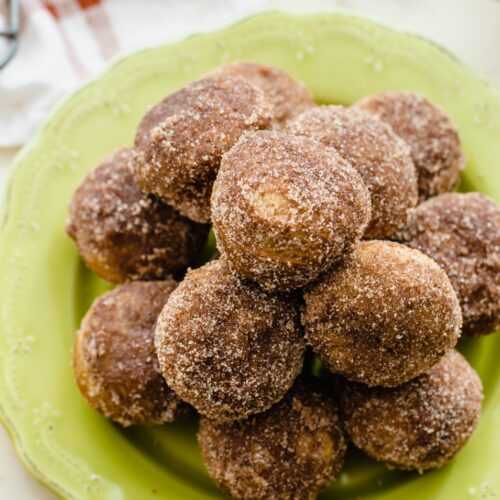 A green plate stacked with apple cider donut holes.