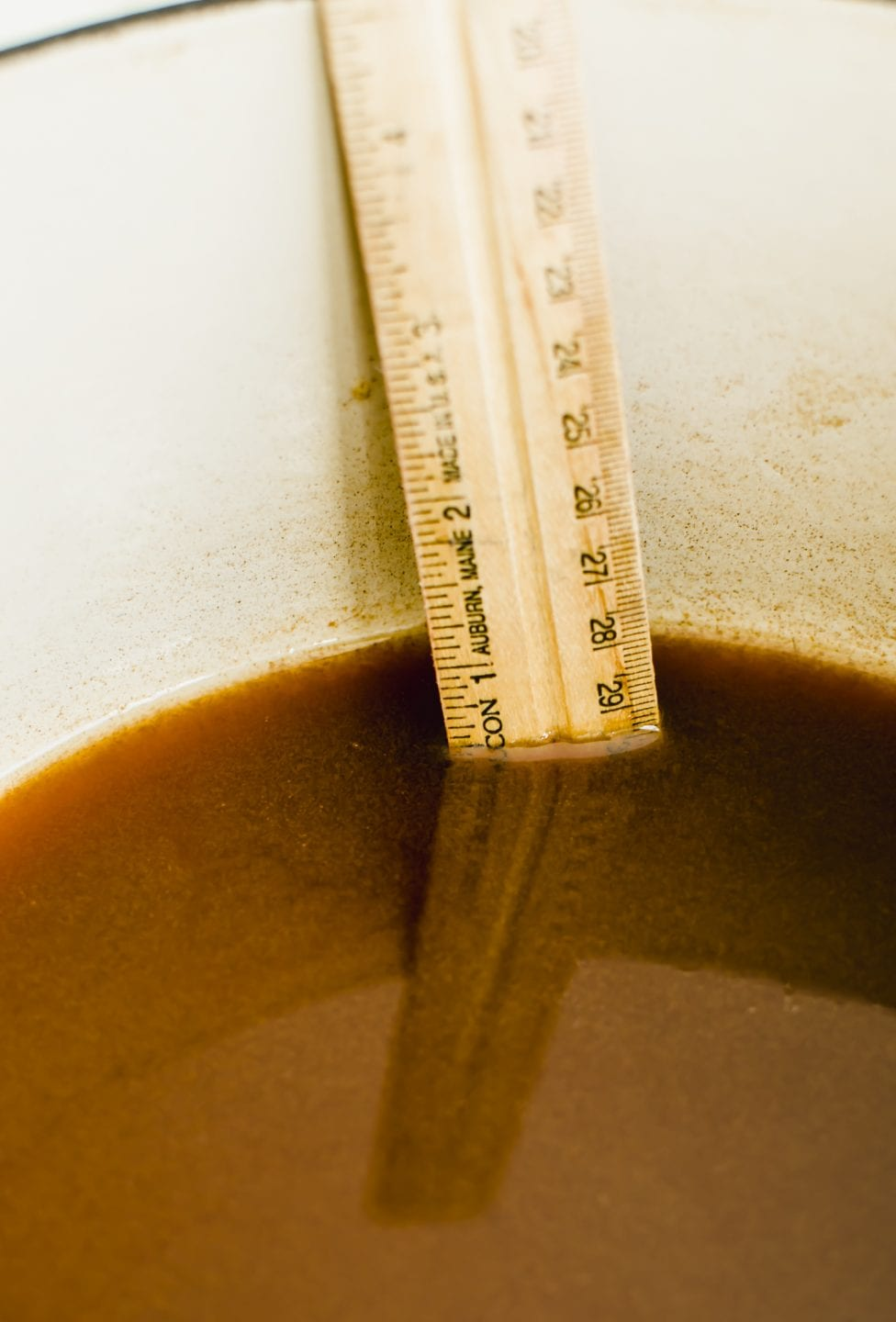 A ruler indicating how much apple cider has reduced down in a pot.