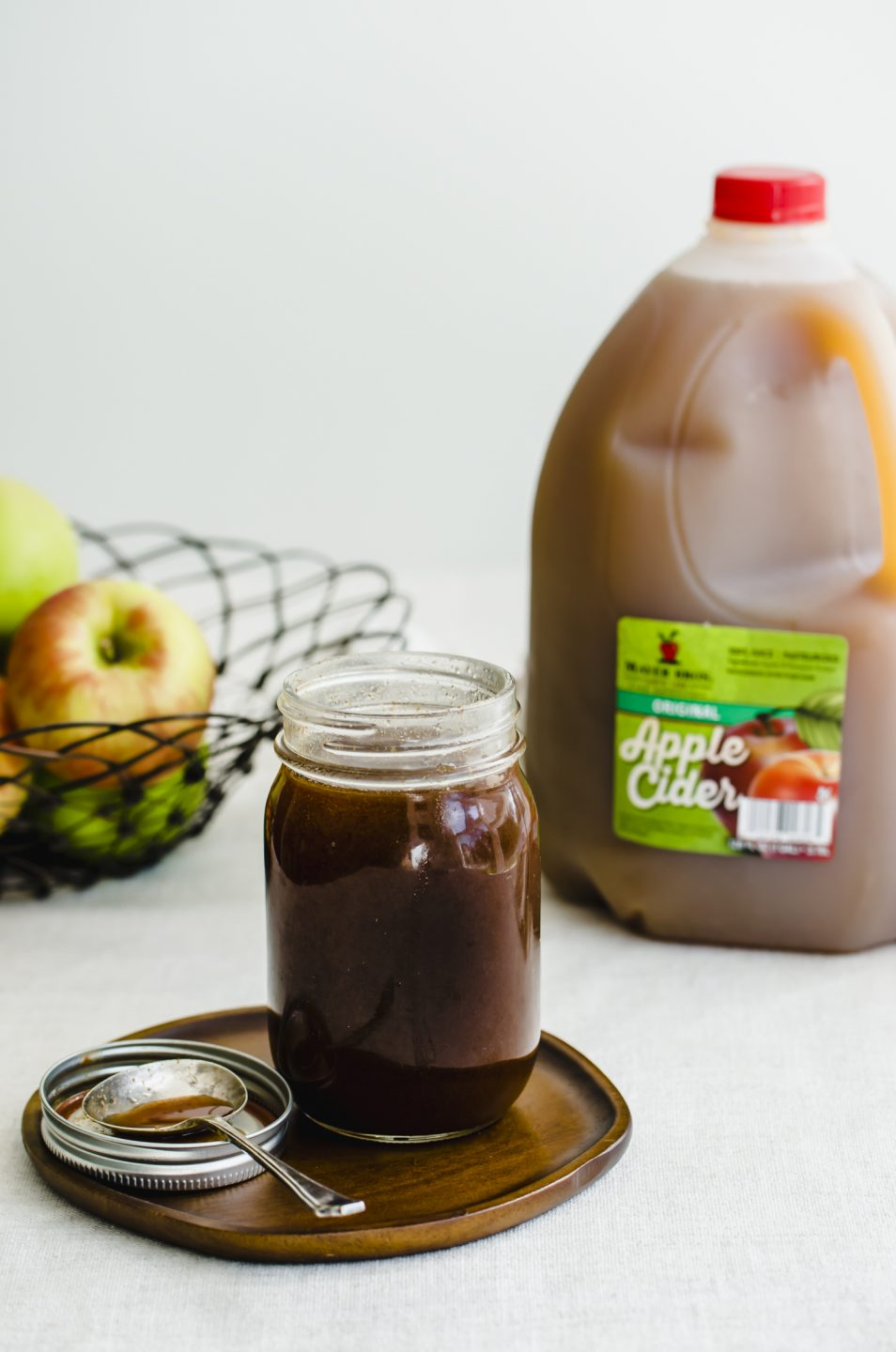 A jar of boiled apple cider syrup on a wooden plate with a jug of apple cider and a basket of fresh apples on the side.