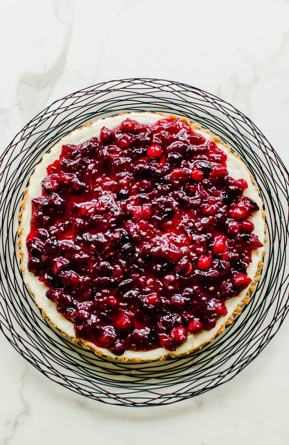 An overhead shot of a cranberry cheesecake tart on a black wire charger.