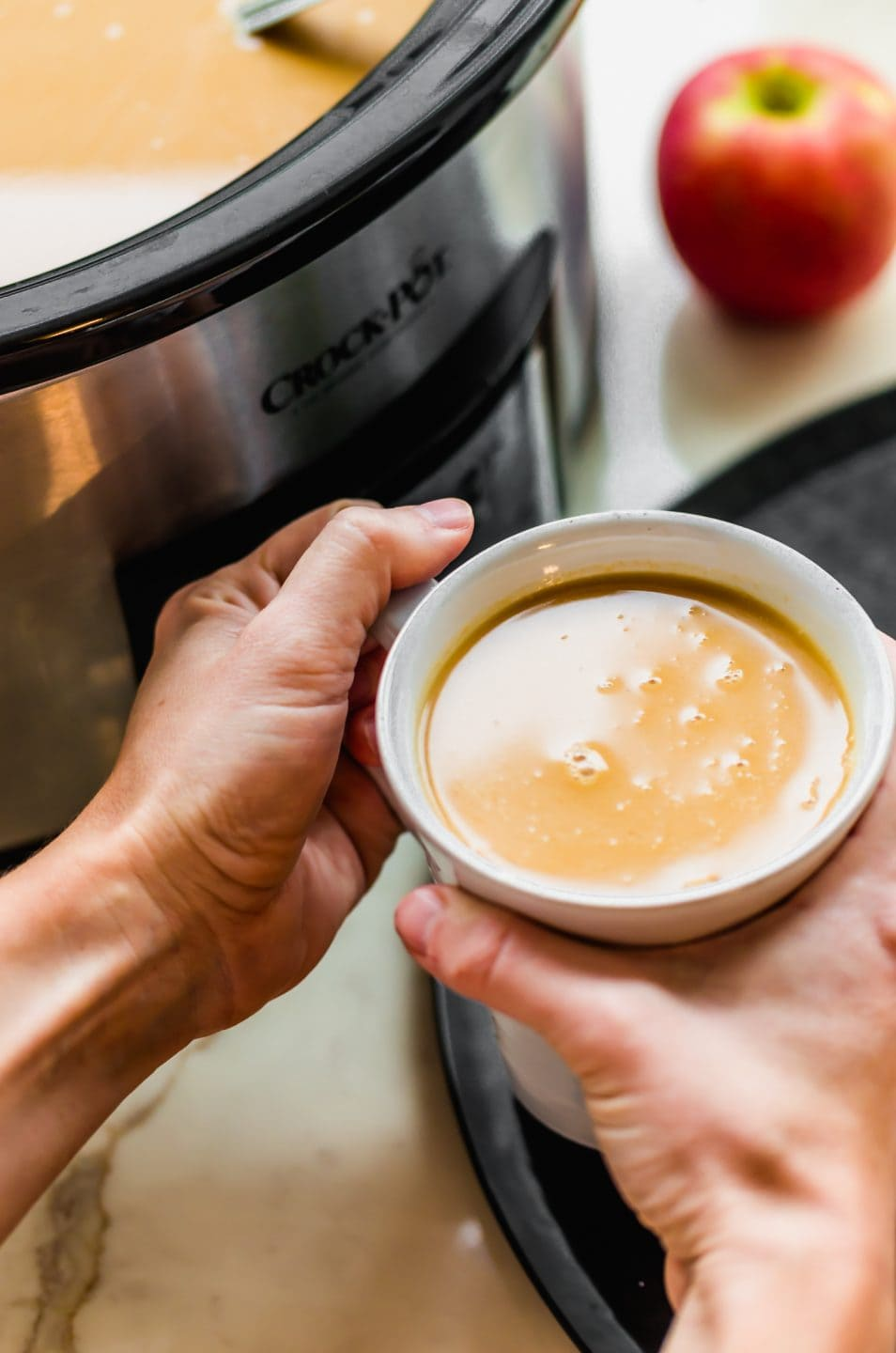 Two hands holding a white mug with salted caramel apple cider next to a Crock Pot.