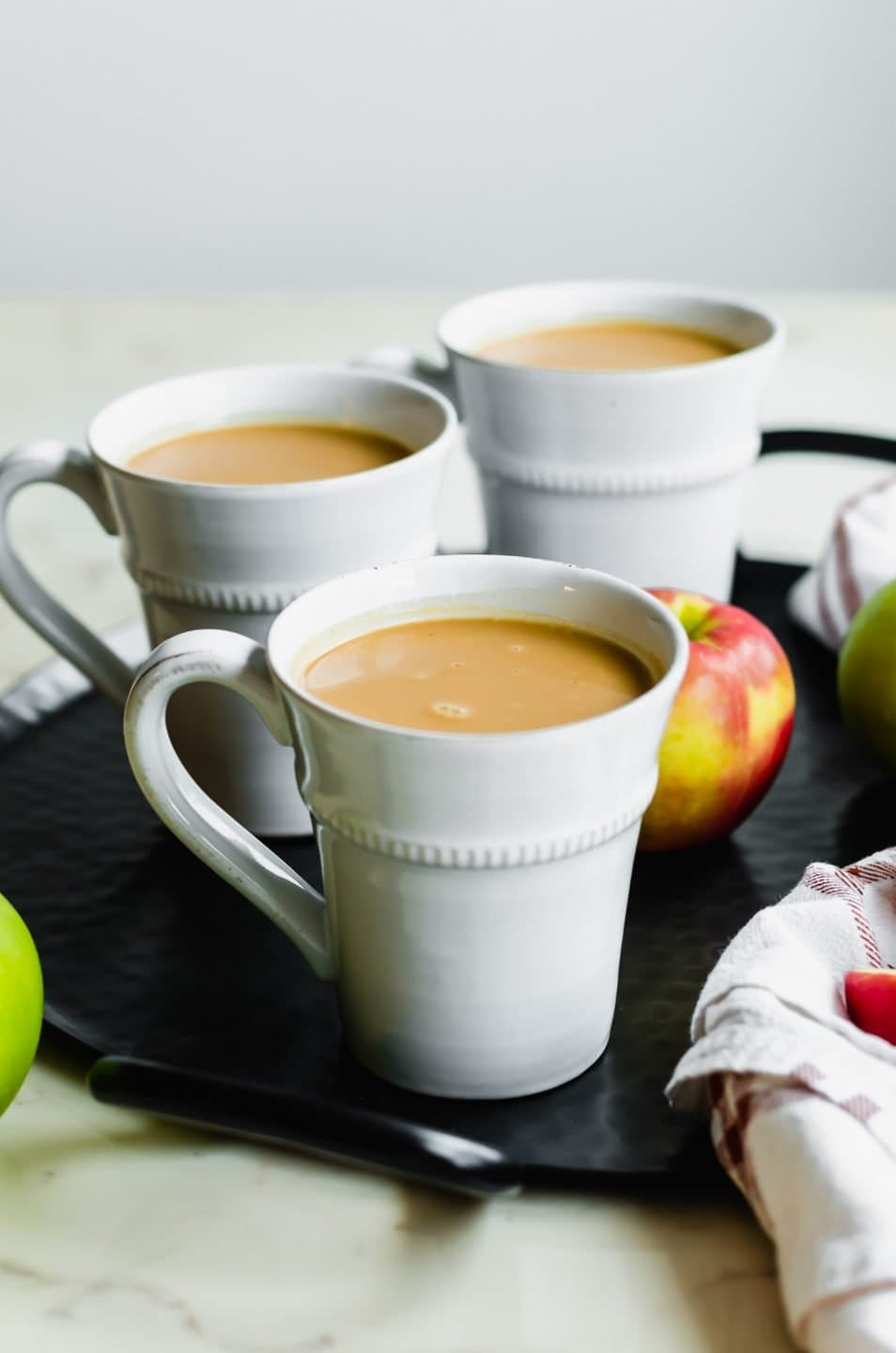 A black iron tray with three white mugs filled with salted caramel apple cider and apples on the side.