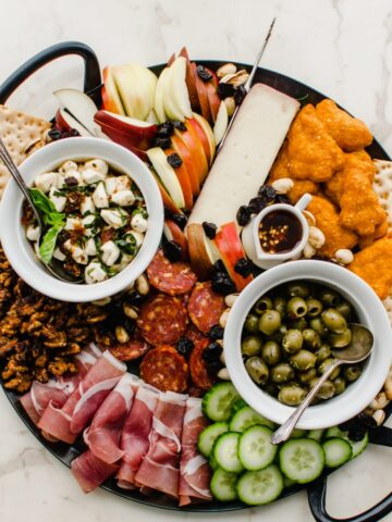 An overhead shot of a black iron platter filled with items for a holiday charcuterie board.